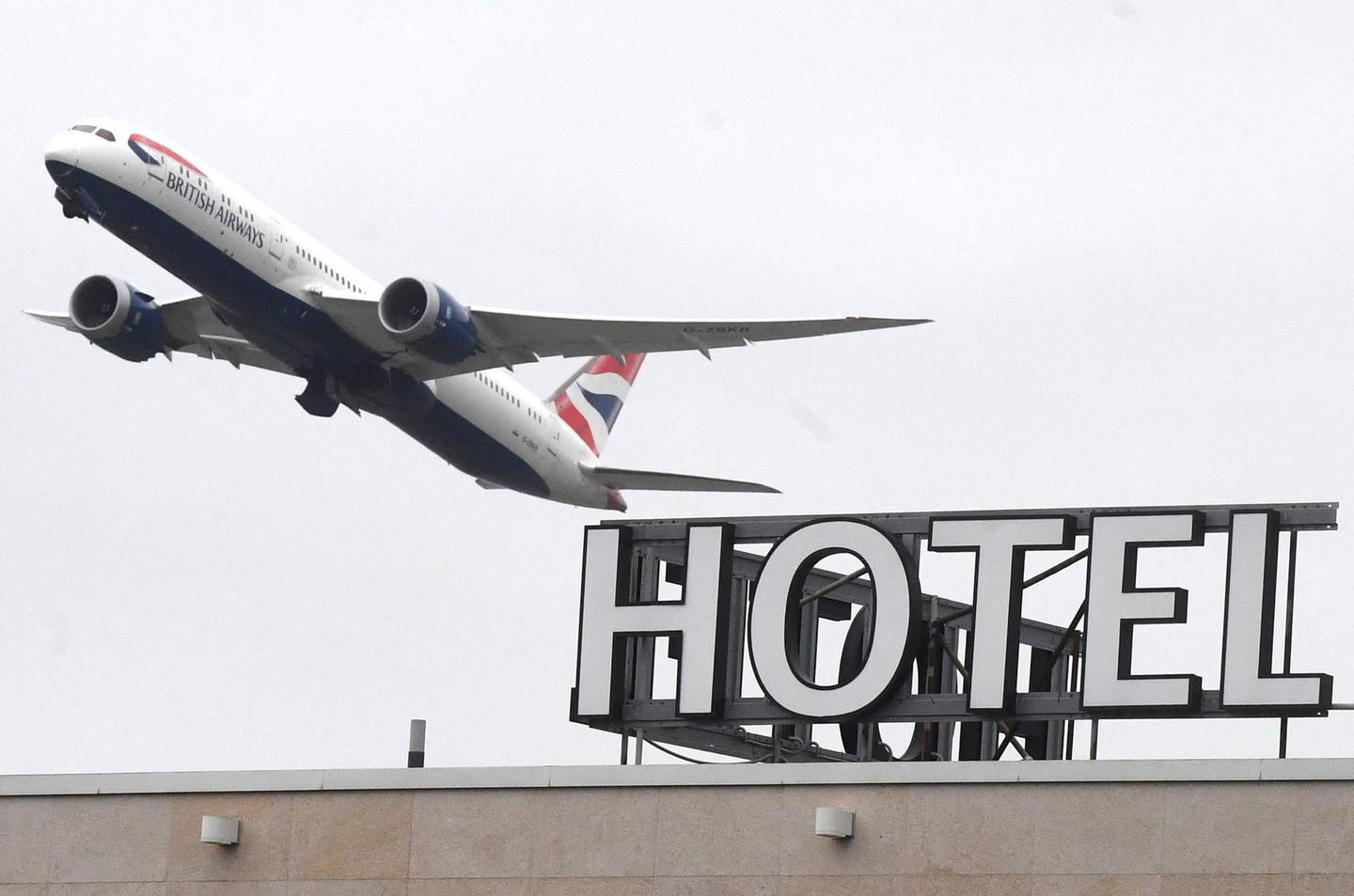 epa08966494 A plane flies over a hotel near Heathrow Airport near London, Britain, 26 January 2021. The British government is expected to approve a plan to require UK citizens to quarantine in a hotel if they arrive in England from high-risk countries.  EPA/NEIL HALL