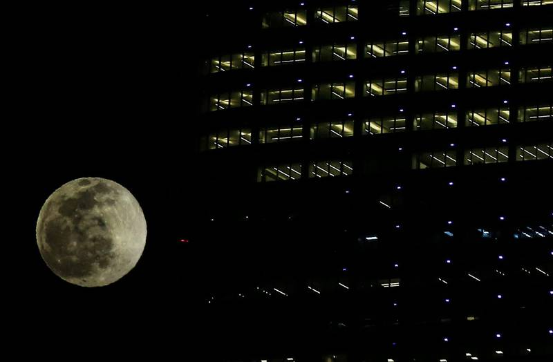 The wolf moon, the first moon of the year rises behind Al-Hamra tower in Kuwait City, on January 28, 2021. / AFP / YASSER AL-ZAYYAT