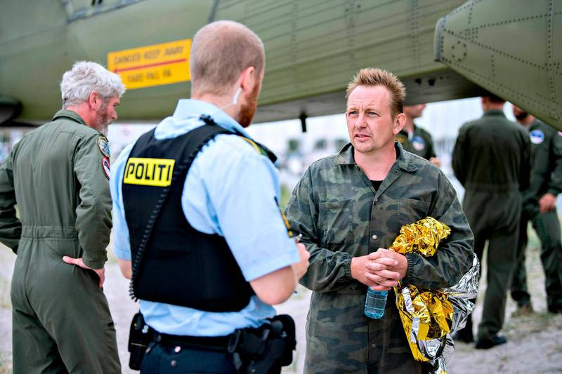 """(FILES) This file photo taken on August 11, 2017 shows Peter Madsen (R), builder and captain of the private submarine """"UC3 Nautilus"""" talking to a police officer in Dragoer Harbor south of Copenhagen, following a major rescue operation after the submarine sank in the sea outside Copenhagen Harbor. Danish prosecutors on January 16, formally charged inventor Peter Madsen with last year's murder of Swedish journalist Kim Wall, whose dismembered body parts were found at sea after she interviewed him on his homemade submarine. Madsen, who was arrested and detained shortly after Wall's disappearance in August, has admitted cutting up her body and dumping it at sea but has denied intentionally killing her.  / AFP PHOTO / Scanpix Denmark / Bax Lindhardt / Denmark OUT"""