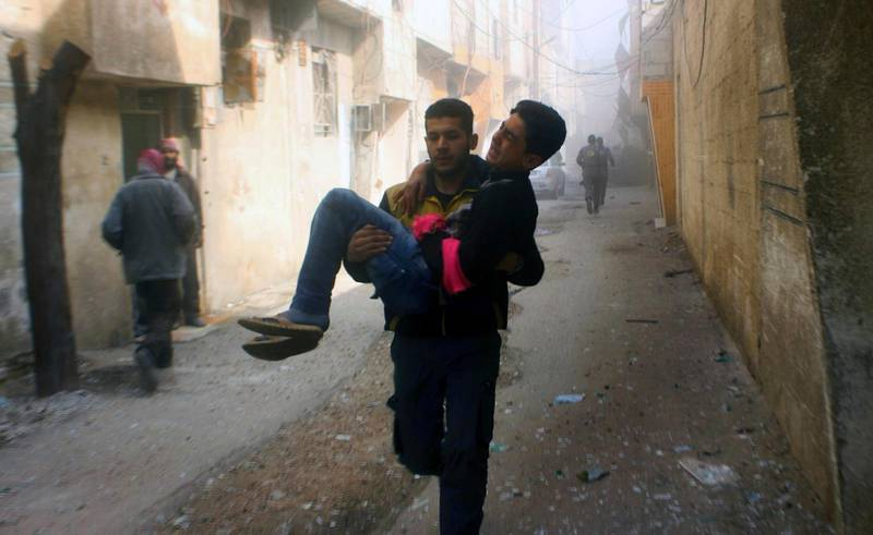 This photo released on Saturday, Feb 24, 2018 by the Syrian Civil Defense group known as the White Helmets, shows members of the Syrian Civil Defense group carrying a young man who was wounded during airstrikes and shelling by Syrian government forces, in Ghouta, a suburb of Damascus, Syria. A new wave of airstrikes and shelling on eastern suburbs of the Syrian capital Damascus left at least 22 people dead and more than a dozen wounded Saturday, raising the death toll of a week of bombing in the area to nearly 500, including scores of women and children. (Syrian Civil Defense White Helmets via AP)