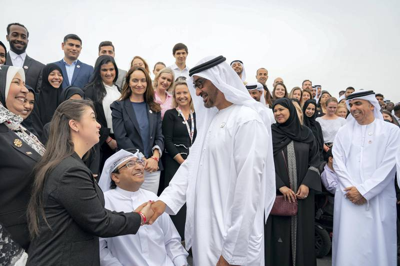 ABU DHABI, UNITED ARAB EMIRATES - March 25, 2019: HH Sheikh Mohamed bin Zayed Al Nahyan, Crown Prince of Abu Dhabi and Deputy Supreme Commander of the UAE Armed Forces (3rd L), greets Rahma Khaled, Egyptian TV host and person of determination (L), during a Sea Palace barza. Seen with Majid Al Usaimi, National Director of the Special Olympics UAE (2nd L).  ( Ryan Carter / Ministry of Presidential Affairs ) ---