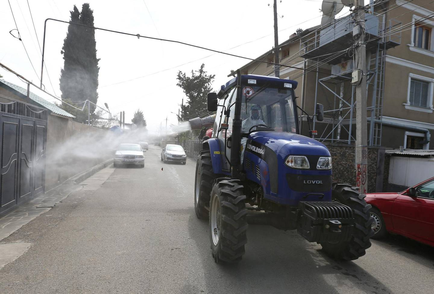 A tractor driven by a worker wearing a protective suit sprays disinfectant on the street to prevent the spread of coronavirus disease (COVID-19), in Marneuli near Tbilisi, Georgia March 25, 2020. REUTERS/Irakli Gedenidze