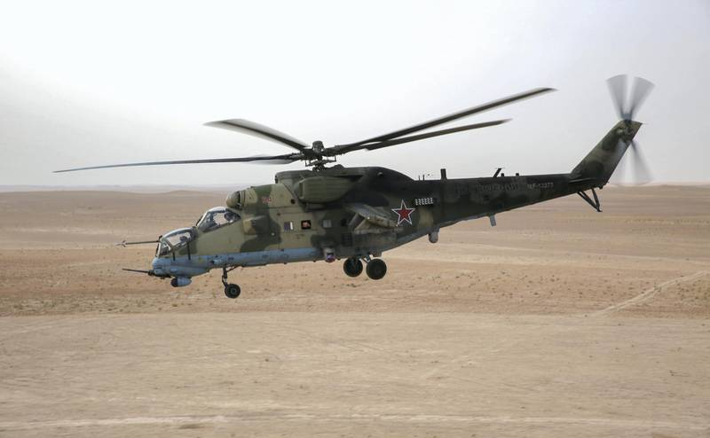 """A picture taken from a helicopter during a press tour provided by the Russian Armed Forces on September 15, 2017 shows a Russian Mil Mi-24 """"Hind"""" attack helicopter flying in the eastern Syrian region of Deir Ezzor. (Photo by Dominique DERDA / France2 / AFP)"""