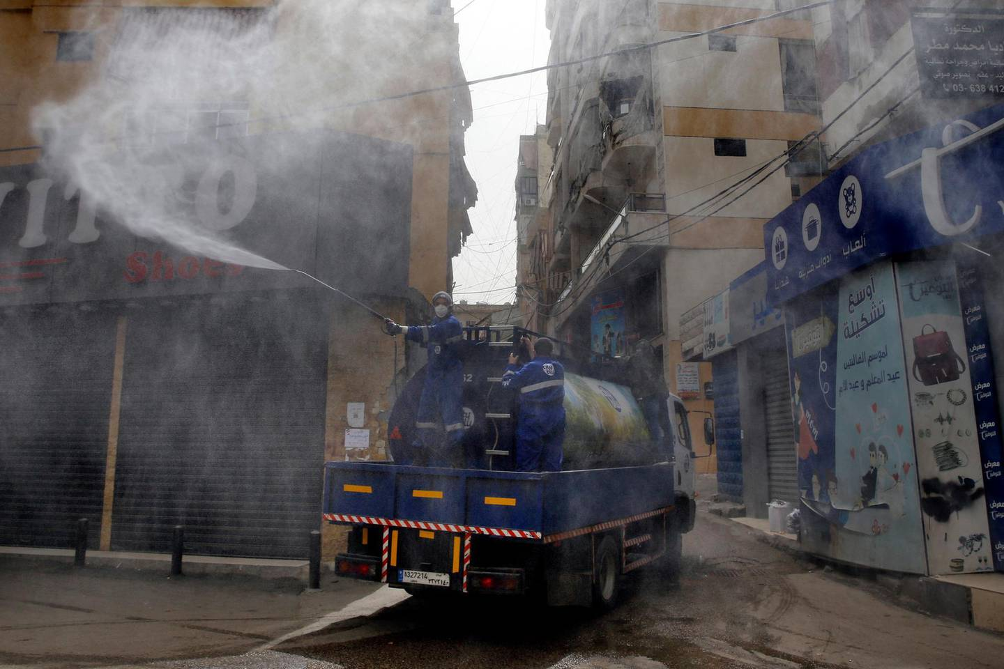 In this Friday, March 27, 2020 photo, members of the Islamic Health Society, an arm of the Iran-backed militant Hezbollah group sprays disinfectants as a precaution against the coronavirus, in a southern suburb of Beirut, Lebanon. Hezbollah has mobilized the organizational might it once deployed to fight Israel or in Syria's civil war to battle the spread of the novel coronavirus. It aims to send a clear message to its Shiite supporters that it is a force to rely on in times of crisis -- particularly after it suffered a series of blows to its prestige. (AP Photo/Bilal Hussein)