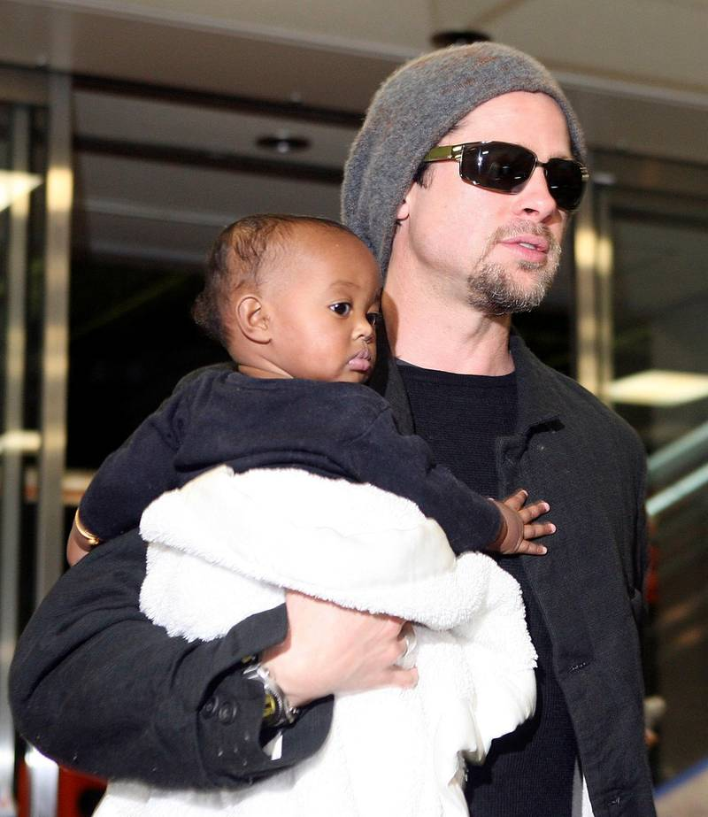 """NARITA, JAPAN - NOVEMBER 27:  Actor Brad Pitt holds Zahara Marley Jolie (Angelina Jolie's daughter) as they arrive at the New Tokyo International Airport on November 27, 2005 in Narita, Japan. Pitt and Angelina Jolie are in Japan to promote a film """"Mr. and Mrs. Smith.""""  (Photo by Koichi Kamoshida/Getty Images)"""
