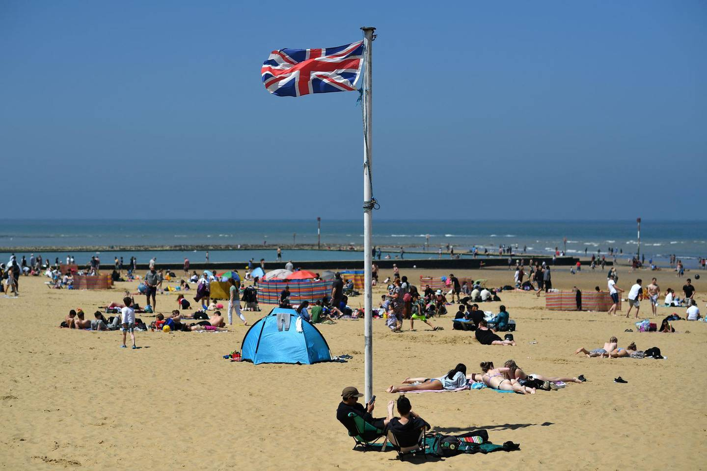 A Union flag flutters in the breeze as sunbathers take advantage of the fine weather on the beach on the coast at Margate, east of London on May 31, 2021, as fine and dry conditions continue in the UK on what could be the hottest day of the year so far.  / AFP / Ben STANSALL