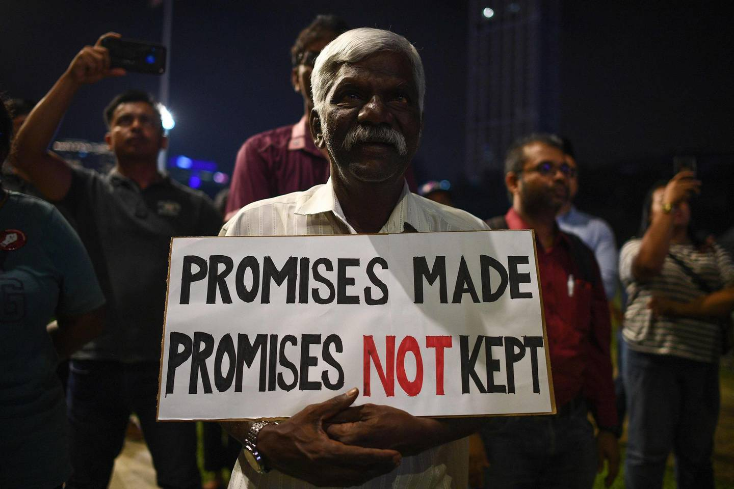 A man holds a sign at a protest against a national government being formed without new elections at Independence Square in Kuala Lumpur on February 25, 2020. Intense political jockeying is underway to form a new government in Malaysia after Mahathir Mohamad, the world's oldest leader, resigned then was appointed interim leader. / AFP / Mohd RASFAN