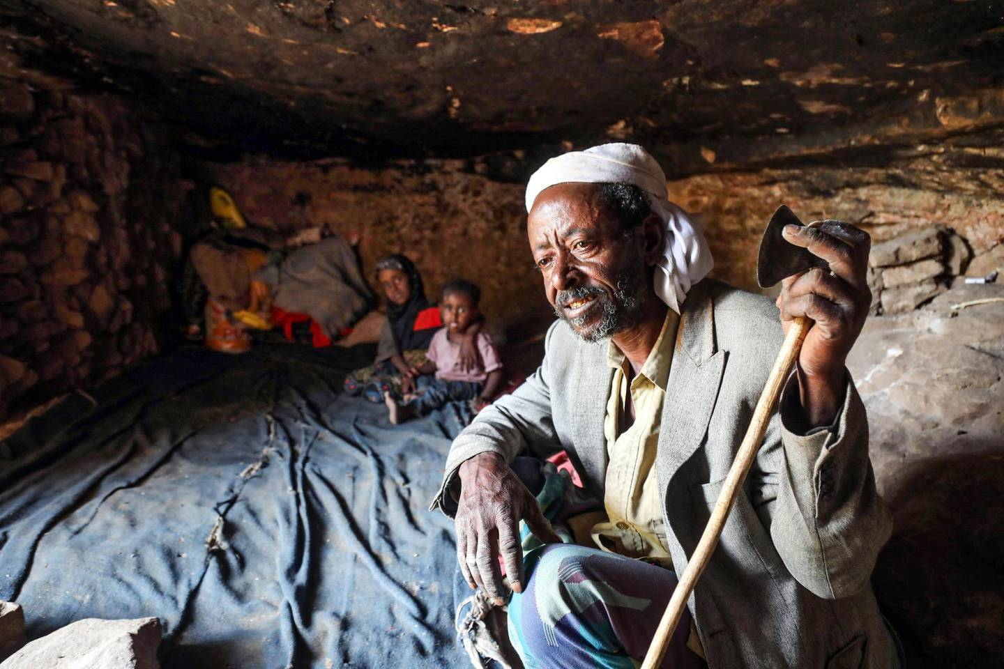 A man and children sit in a cave where a Yemeni family has sought refuge due to poverty and lack of housing, west of the suburbs of Yemen's third-city of Taez on December 2, 2020.  / AFP / AHMAD AL-BASHA