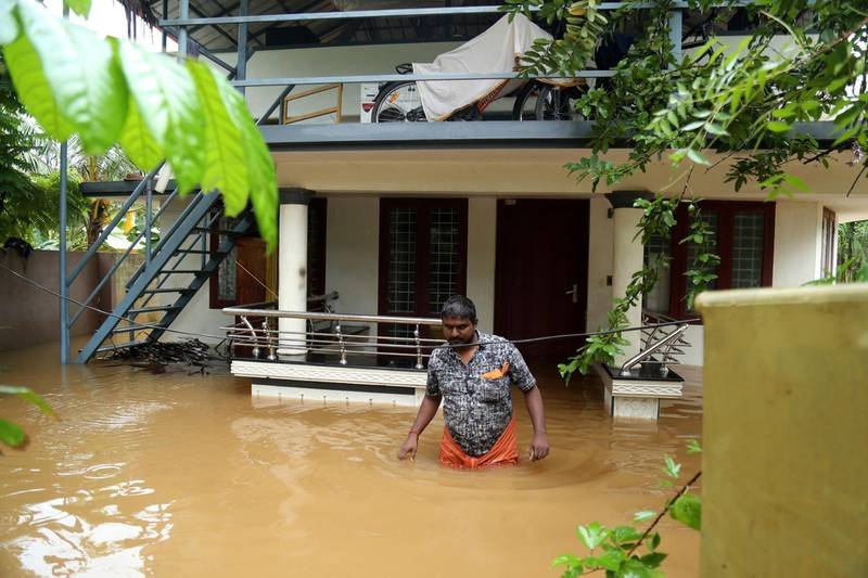 epa07763639 An Indian man walks in a flooded street outside a house in Kochi, Kerala, India, 09 August 2019. According to news reports, the operation of the Cochin International Airport has been stopped till 11 August after Heavy rains saw water levels rise in the Periyar river, near Cochin airport.  EPA/PRAKASH ELAMAKKARA