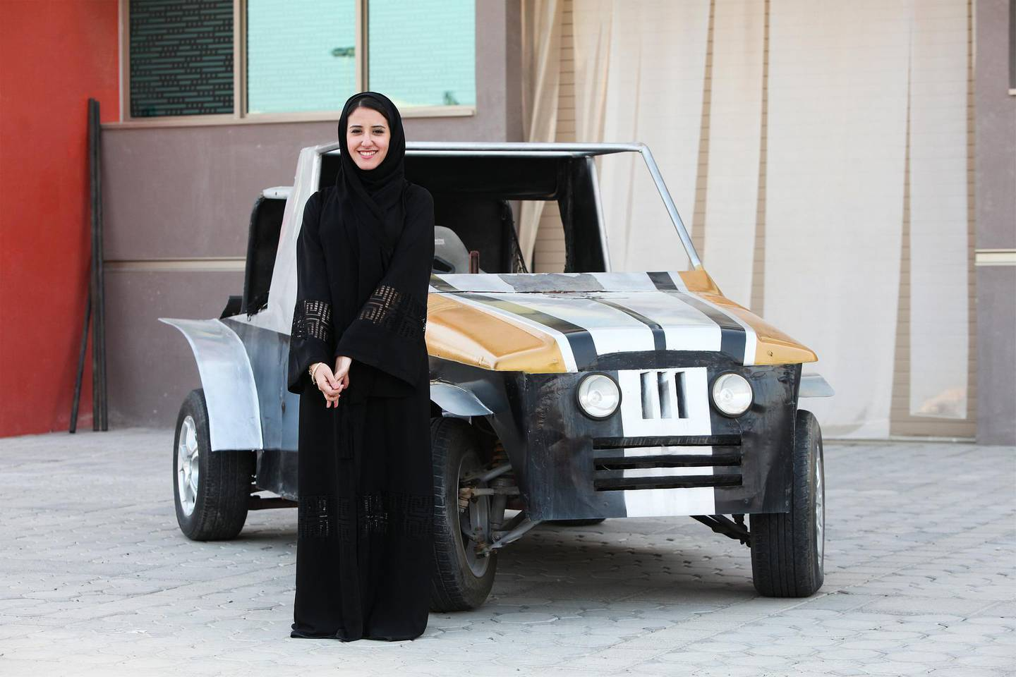 """Al Ain, UAE, October 31, 2013:Reem Al Marzouqi saw a video of an armless pilot in the U.S. airforce 5 years ago. After finding out that this pilot could fly but not drive, she decided to make a car that would only require the use of one's feet. It is seen here along with its """"innovator"""" (she did not want to use the word invention). Ms. Marzouqi, at the age of 22, is also a fashion designer and is currently majoring in Architecture at the UAE University (UAEU), where the shoot took place. Lee Hoagland/The National *** Local Caption ***  LH1031_FOOT_CAR_03.jpg"""