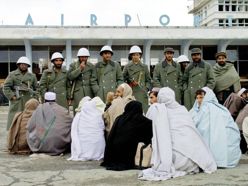 401223 03: Armed police watch over Afghan pilgrims as they wait outside Kabuls Airport to board flights to Saudi Arabia to partake in the Haj pilgrimage February 18, 2002 in Kabul, Afghanistan. Thousands of pilgrims from all over Afghanistan have been waiting for days to board flights to travel to Mecca. (Photo by Natalie Behring/Getty Images)