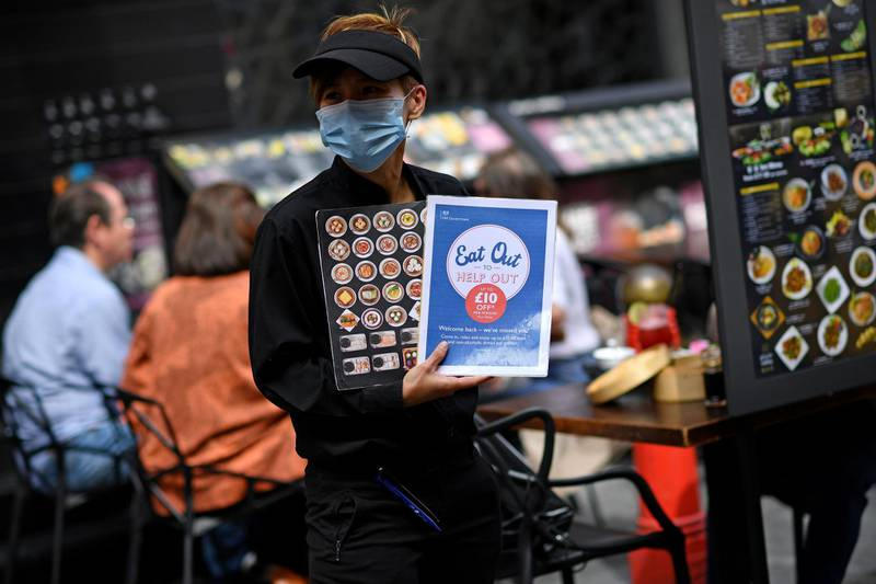 """A waiter wearing a protective face mask displays """"eat out to help out"""" information in a restaurant in the chinatown area of Soho in London on August 26, 2020, as businesses in the busy London area try to keep working despite the novel coronavirus COVID-19 pandemic. Britain's economy shrank by one fifth in the second quarter, more than any European neighbour, as the lockdown plunged the country into its deepest recession on record and tourists remain reluctant to visit because Britain is the European country worst hit by the coronavirus.     / AFP / Ben STANSALL"""