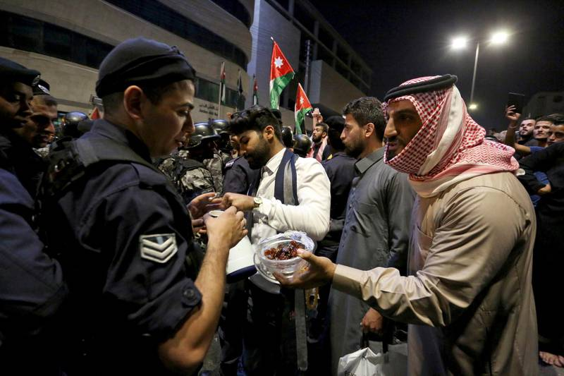 Protesters offer sweets to police officers standing guard during a protest in Amman, Jordan, early Tuesday, June 5, 2018. Jordan's King Abdullah II on Monday accepted the resignation of his embattled prime minister and reportedly tapped a leading reformer as a successor, hoping to quell the largest anti-government protests in recent years, which are also seen as a potential challenge to his two-decade-old rule.(AP Photo/Raad al-Adayleh)