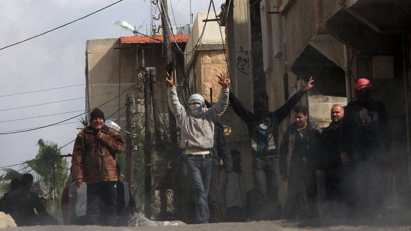 """Anti-government activists gestures as they gather on the streets of Daraa, 100kms south of the capital Damascus on March 23, 2011. Syrian security forces fired on anti-regime protesters near a mosque in then town, killing five and wounding scores, rights activists said as the government blamed a """"gang"""" for the violence.  AFP PHOTO/ANWAR AMRO (Photo by ANWAR AMRO / AFP)"""
