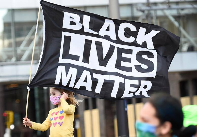 epa09105723 A young girl holds a flag reading 'Black Lives Matter' (BLM) as protesters march through downtown Minneapolis on the first day of opening statements for the murder trial of former Minneapolis police officer Derek Chauvin who was charged in the death of George Floyd, in Minneapolis, Minnesota, USA, 29 March 2021.  EPA/CRAIG LASSIG