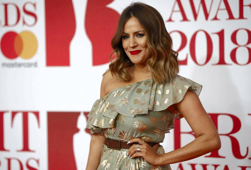 British television presenter Caroline Flack poses on the red carpet on arrival for the BRIT Awards 2018 in London on February 21, 2018. (Photo by Tolga AKMEN / AFP) / RESTRICTED TO EDITORIAL USE – NO POSTERS – NO MERCHANDISE– NO USE IN PUBLICATIONS DEVOTED TO ARTISTS