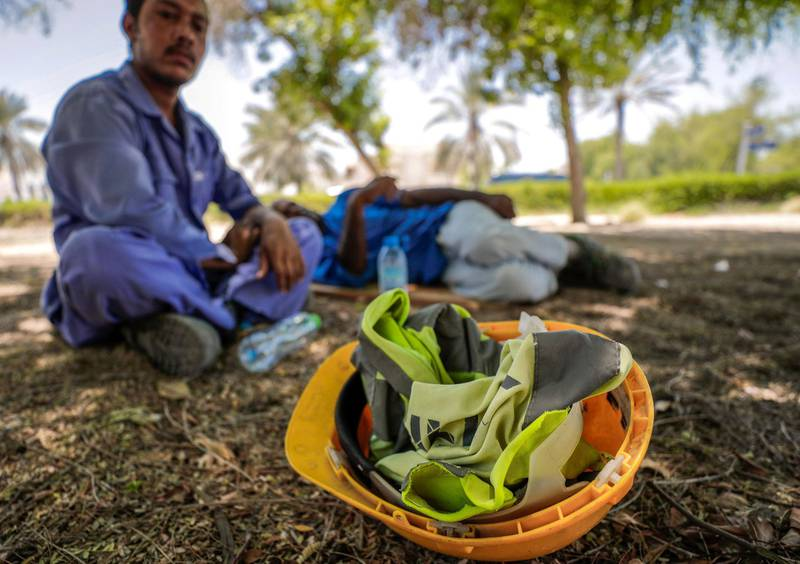Abu Dhabi, United Arab Emirates, June 15, 2019.  The UAE's mandatory midday break for people working outdoors during the summer months will come into force on Saturday. --  Pakistani workers take refuge under the shade of a tree along Al Dhafra street.Victor Besa/The NationalSection:  NAReporter: