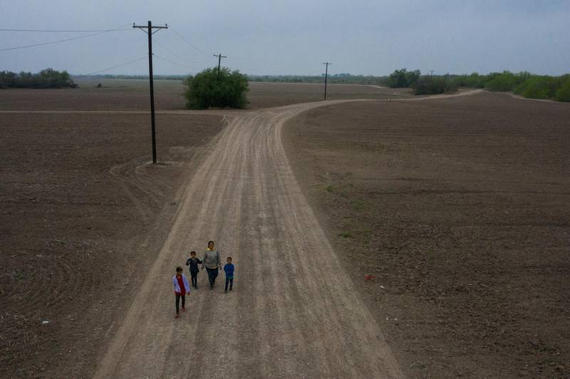 Sonia, an asylum-seeking migrant from Honduras, walks down a dirt road with her three children Jefferson, 9, Scarlet, 7, and David, 6, after they crossed the Rio Grande river into the United States from Mexico on a raft in Penitas, Texas, U.S., March 16, 2021. Picture taken with a drone. REUTERS/Adrees Latif