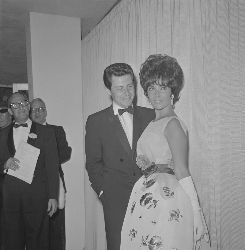 """(Original Caption) Elizabeth Taylor and her new husband, Eddie Fisher, pause to smile broadly before entering the Santa Monica Civic Auditorium, April 17th, for the Academy Award presentations. Miss Taylor has been nominated for the Best Actress award for her leading role in """"Butterfield 8."""" Getty Images"""