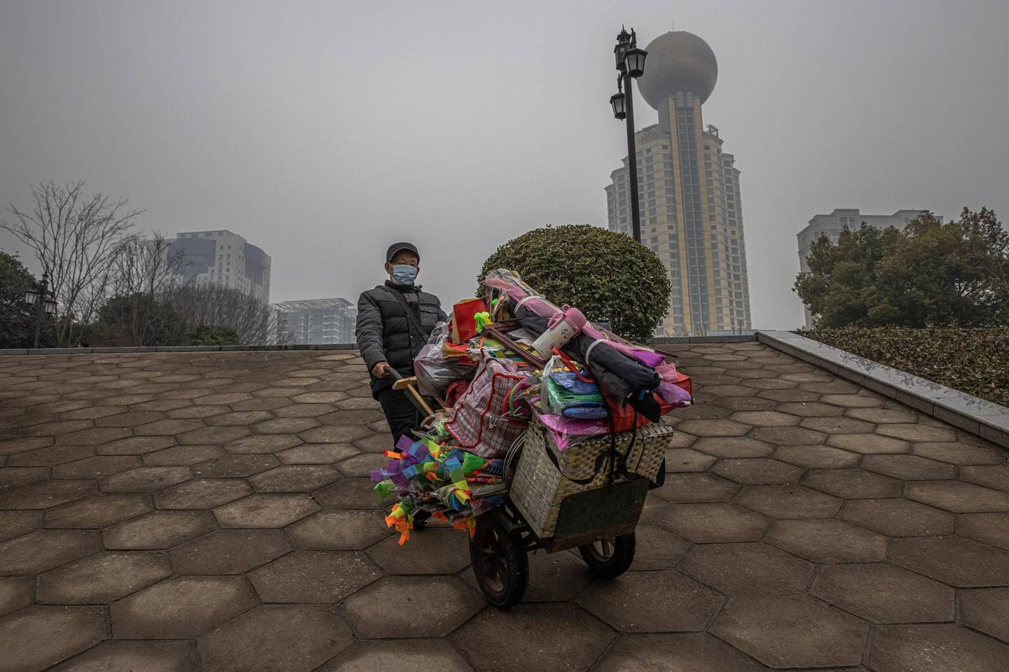 epa08959237 A seller pushes his cart at a riverside park along the Yangtze River on the day of Wuhan's lockdown one-year anniversary, in Wuhan, China, 23 January 2021. The day 23 January 2021 marks the one-year anniversary of the start of a strict 76-day lockdown of the Chinese city of Wuhan, where the novel coronavirus SARS-CoV-2 that causes the COVID-19 disease, was first discovered before spreading across the world into a deadly global pandemic.  EPA/ROMAN PILIPEY