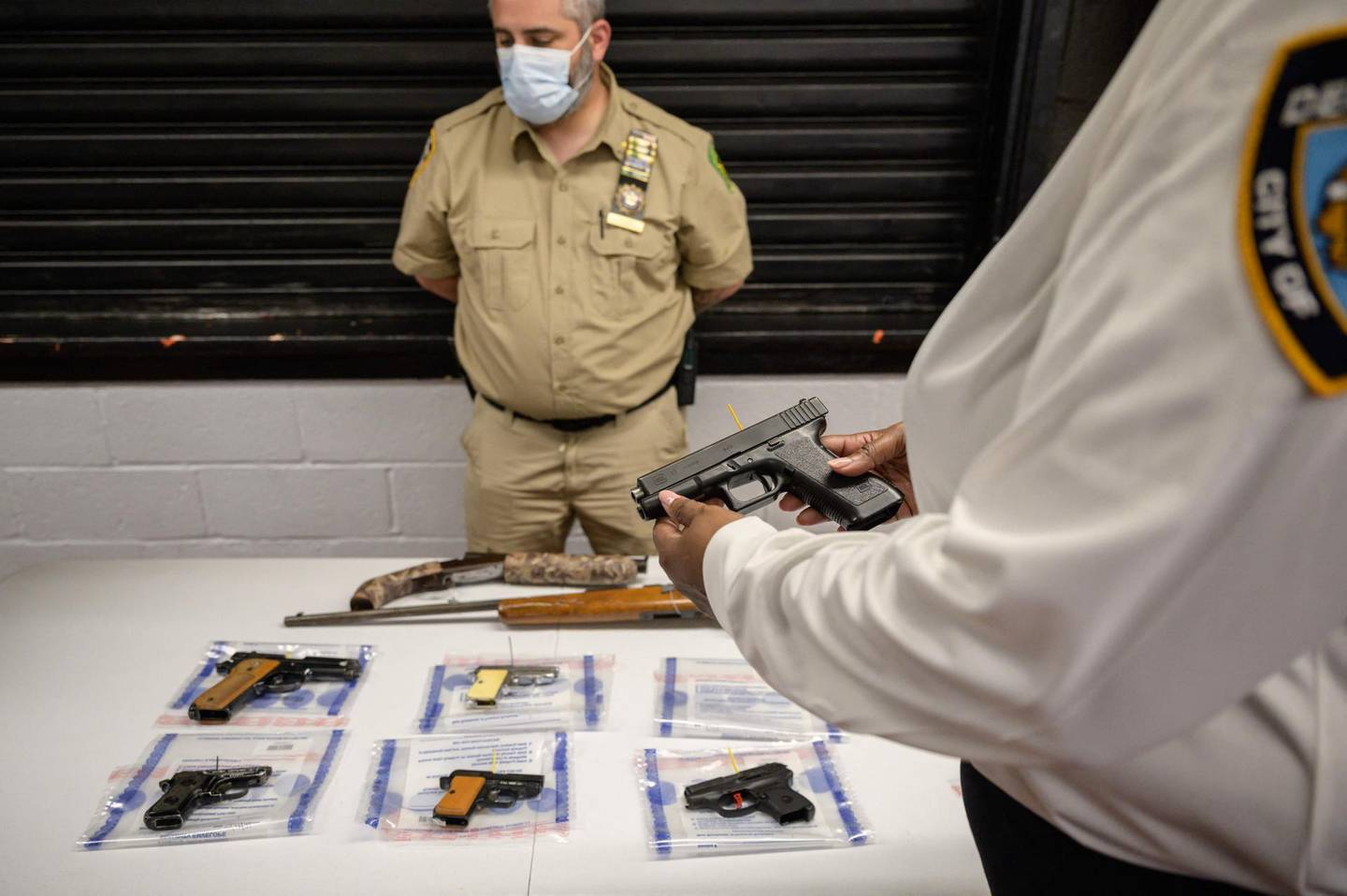 """(FILES) In this file photo taken on May 22, 2021, a Glock 17 pistol, or handgun, is displayed during a gun 'buyback' event held by the New York Police Department (NYPD) and the office of the Attorney General, in the New York borough of Brooklyn. A dozen people were killed and about 50 injured in shootings across the United States over the weekend, after President Joe Biden last month branded the country's gun violence an """"epidemic."""" / AFP / Ed JONES"""