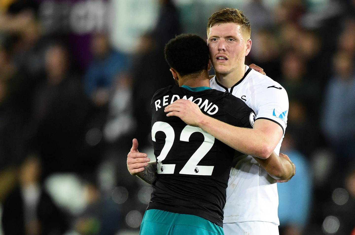 """Soccer Football - Premier League - Swansea City v Southampton - Liberty Stadium, Swansea, Britain - May 8, 2018   Swansea City's Alfie Mawson hugs Southampton's Nathan Redmond after the match   REUTERS/Rebecca Naden    EDITORIAL USE ONLY. No use with unauthorized audio, video, data, fixture lists, club/league logos or """"live"""" services. Online in-match use limited to 75 images, no video emulation. No use in betting, games or single club/league/player publications.  Please contact your account representative for further details."""