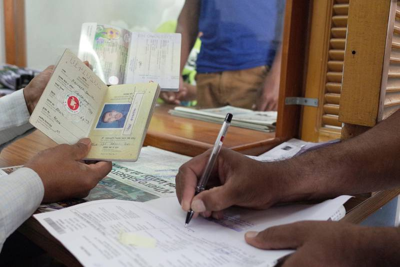 ABU DHABI, UNITED ARAB EMIRATES - - -  October 29, 2015 --- Bangladeshis get their old passports cancelled and new ones issued at the Bangledesh embassy in Abu Dhabi on Thursday, October 29, 2015. More than 50,000 Bangladeshis have yet to convert their old handwritten passports with the machine readable digital passports in the UAE. The international deadline for replacing the old passport document ends on November 24, 2015.     ( DELORES JOHNSON / The National ) *** Local Caption ***  DJ-291015-NA-Passports-006.jpg