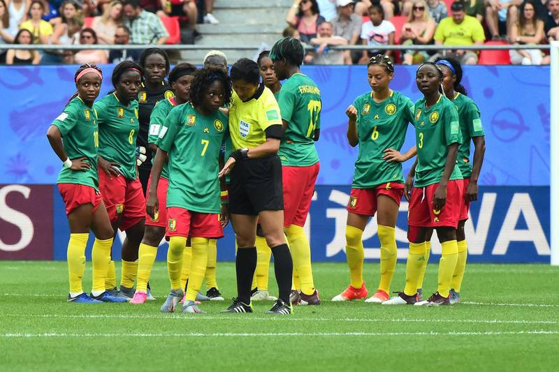 VALENCIENNES, FRANCE - JUNE 23:  (C) Gabrielle Aboudi Onguene of Cameroon speaks with Referee Qin Liang during the 2019 FIFA Women's World Cup France Round Of 16 match between England and Cameroon at Stade du Hainaut on June 23, 2019 in Valenciennes, France.  (Photo by Pier Marco Tacca/Getty Images)