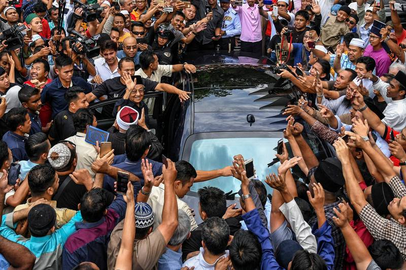 epaselect epa06727115 Malaysian newly elected Prime Minister Mahathir Mohamad (C) is surrounded by his supporters after Friday prayers in Kuala Lumpur, Malaysia, 11 May 2018. Malaysia's Pakatan Harapan alliance lead by former Prime Minister Mahathir Mohamad has won a historic election victory, leading to his return to power at the age of 92.  EPA/STR