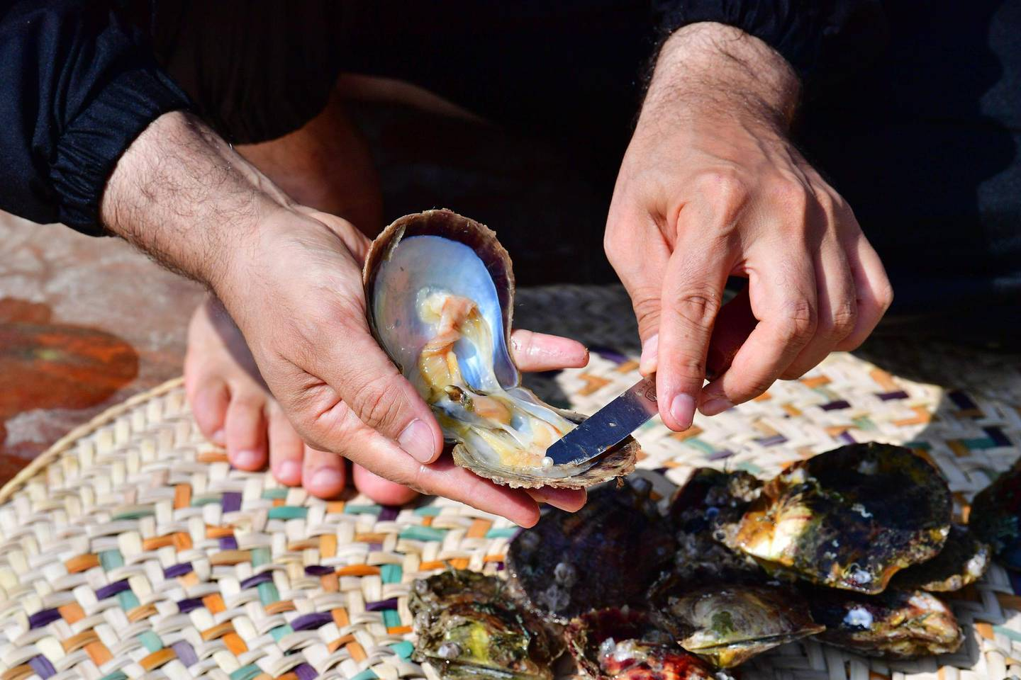 Emirati Abdullah al-Suwaidi displays a pearl found in a oyster at the Suwaidi's pearl farm, off the coast of al-Rams in the northern emirate of Ras al-Khaimah, on October 31, 2019. Suwaidi's project, one of a handful of operations in the United Arab Emirates, comes against a backdrop of increasing awareness of cultural traditions, such as falconry and camel racing, and efforts to promote and preserve them. Last month, Abu Dhabi authorities announced that the world's oldest natural pearl, found just off the capital at Marawah Island, would be displayed for the first time at the Louvre Abu Dhabi, the local outpost of the famous Paris museum.  / AFP / GIUSEPPE CACACE