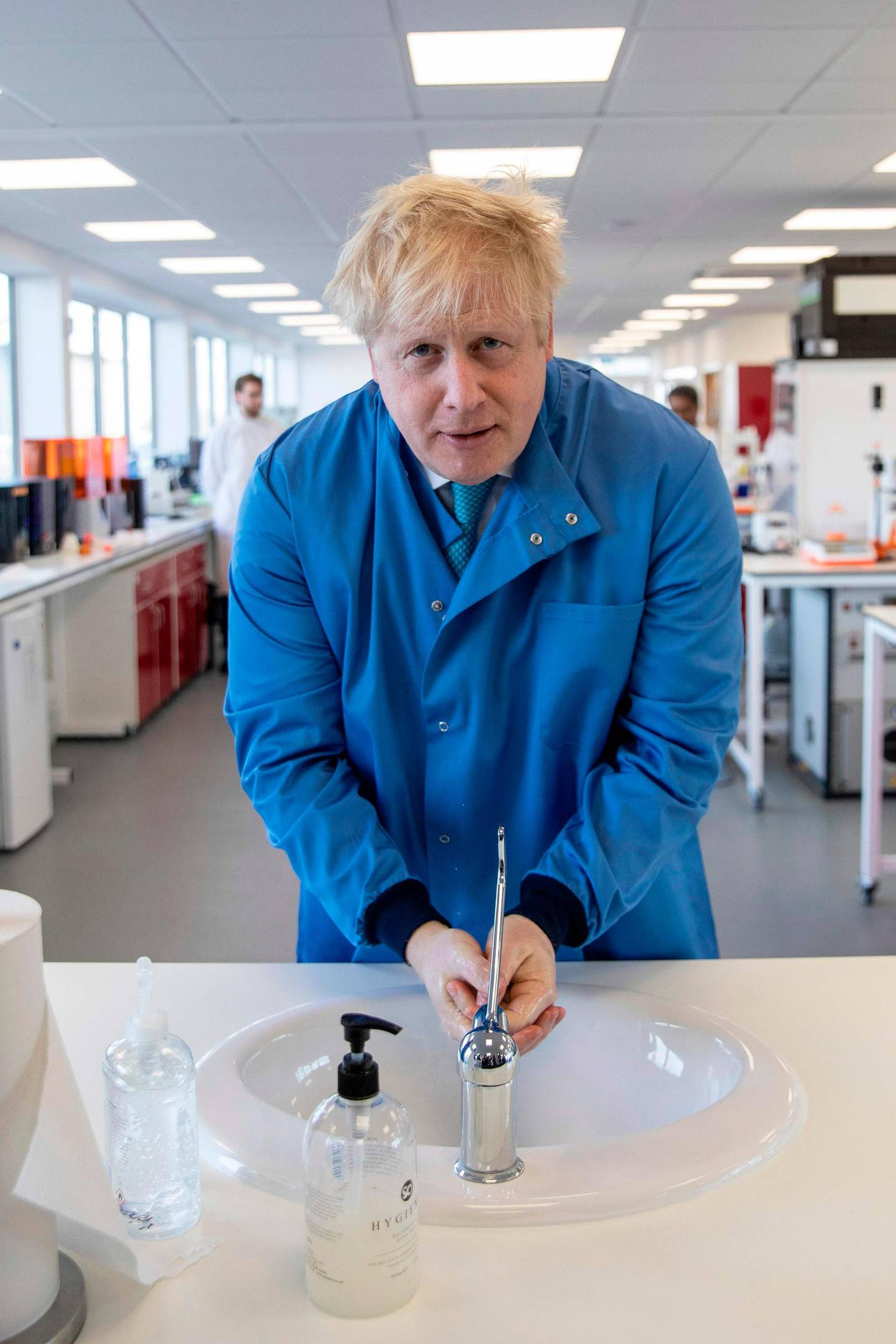 Britain's Prime Minister Boris Johnson washes his hands during a visit to the Mologic Laboratory in the Bedford technology Park, north of London on March 6, 2020. The Prime Minister pledged a further £46 million for research into a coronavirus vaccine and rapid diagnostic tests during the visit to the Laboratory, where British scientists are working on ways to diagnose coronavirus.  / AFP / POOL / Jack Hill