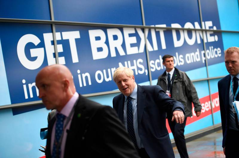 """Britain's Prime Minister Boris Johnson (C) walks outside the Manchester Central convention complex in Manchester, northwest England on September 29, 2019, on the first day of the annual Conservative Party conference. Embattled British Prime Minister Boris Johnson gathered his Conservative party Sunday for what could be its final conference before an election, promising to """"get Brexit done"""". / AFP / Oli SCARFF"""