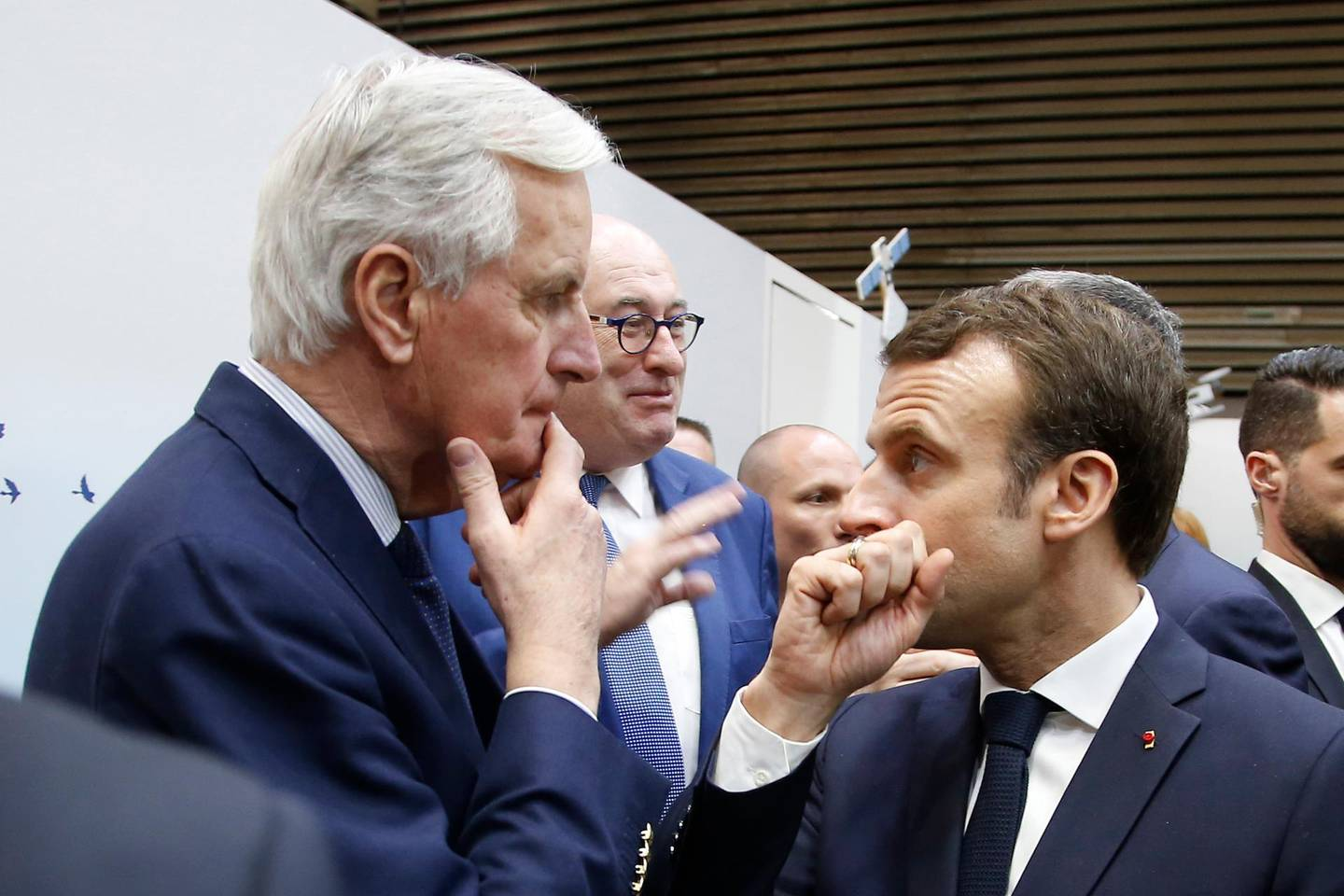 FILE - In this Saturday, Feb. 23, 2019 file photo, French President Emmanuel Macron, right, whispers to European Union chief Brexit negotiator Michel Barnier as he visits the International Agriculture Fair, in Paris, France. He's known throughout most of Europe as Mr. Brexit, but not so well known at home in France. With a new book out this week, and interviews in national media, Michel Barnier is trying to raise his profile ahead of next April's presidential election. (AP Photo/Michel Euler, Pool, File)