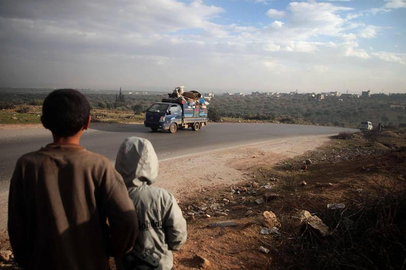 TOPSHOT - Boys look on at a truck loaded with furniture and belongings as in the village of al-Mastumah, about seven kilometres south of the city of Idlib on December 24, 2019, as Syrian families from the south of Idlib province drive through towards the Syrian-Turkish border fleeing the assault led by government forces and their allies.  / AFP / Aaref WATAD