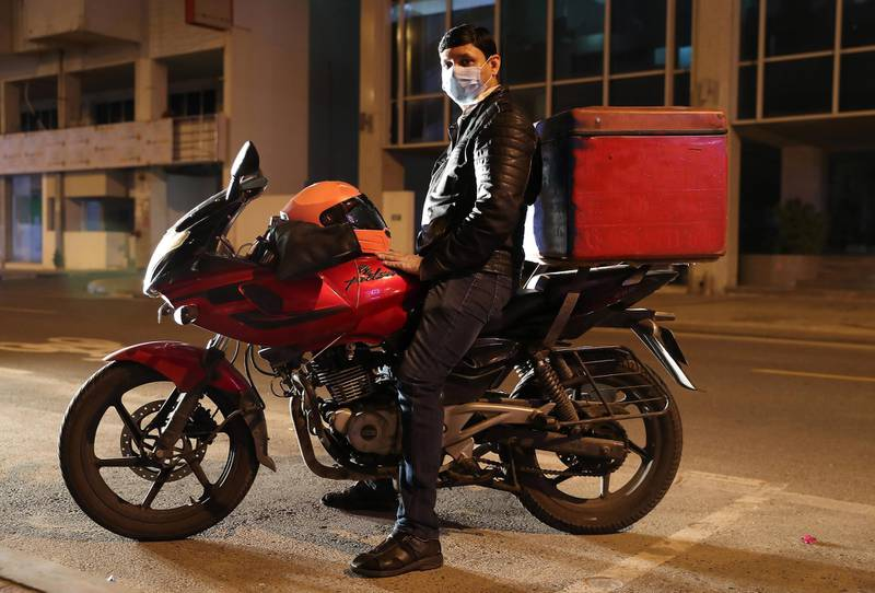 DUBAI, UNITED ARAB EMIRATES , March 25 – 2020 :-  Sanjay Kumar, 35 years old from India working as a delivery man at the Indian restaurant called 'Manvaar' in Al Karama near Karama Fish Market in Dubai. He is married and has 2 sons. Manvaar restaurant is packing the food for delivery in two layers of carry bag in these circumstances so that customer can get away from the first carry bag and take their food packets. Manvaar restaurant is using surface sanitizer SS02 which used to sanitize kitchen in the restaurants approved by the authorities in Dubai. After every one hour they are sanitizing the Kitchen as a preventive measure against coronavirus in Dubai. All the restaurants closed for dining until further notice. Sanjay Kumar said now wherever he delivers the food mostly he left the food packet at the security reception or at the reception of the building as the customer pays most of the orders online in advance. Manvaar restaurant is handing over food orders to their delivery men through one of the window at the restaurant and placed sanitizer for them to use it after every order as a safety measure against coronavirus. He is using facemask, gloves, washing and sanitizing his hands regularly for his safety.  (Pawan Singh / The National) For Unsung Hero of UAE Photo Feature