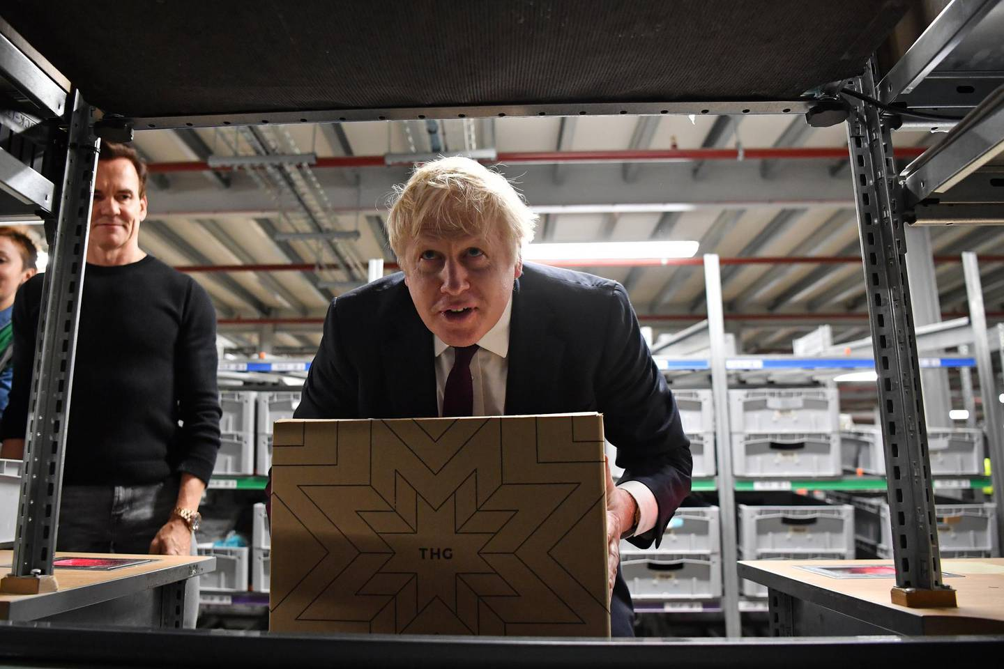 WARRINGTON, ENGLAND - DECEMBER 10: Britain's Prime Minister and Conservative party leader Boris Johnson (C) moves a box in a fulfillment centre for The Hut Group (THG) during a general election campaign event on December 10, 2019 in Warrington, United Kingdom. The U.K will go to the polls in a general election on December 12. (Photo by Ben Stansall - WPA Pool / Getty Images)