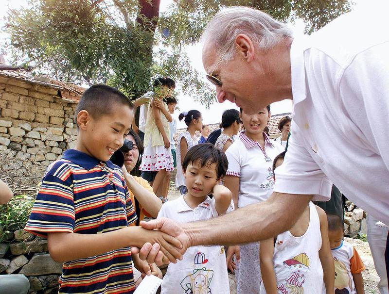 US Senate Foreign Relations Committee Chairman Joseph Biden (R) shakes hands with seven-year-old Gao Shan, the boy Biden proclaimed as the future president of China, during a visit to the village of Yanzikou, north of Beijing, 10 August 2001.  After meeting Chinese leaders for two days, Biden and his delegation left Beijing to look at life in the countryside, where 70 percent of China's population lives.    AFP PHOTO/POOL (Photo by GREG BAKER / POOL / AFP)