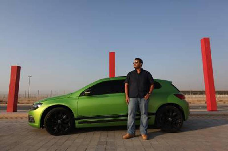 """United Arab Emirates - Dubai - November 1, 2010.  ARTS & LIFE: Khaled Wazzan (cq-al), 22, of Dubai, poses for his portrait next to his Volkswagen Scirocco in Dubai Motor City on Monday, November 1, 2010. """"It captures attention when you're driving,"""" said Wazzan, a business management student at American University Dubai. When asked whether he likes attention, Wazzan replied, """"Of course! Who doesn't?""""  Amy Leang"""