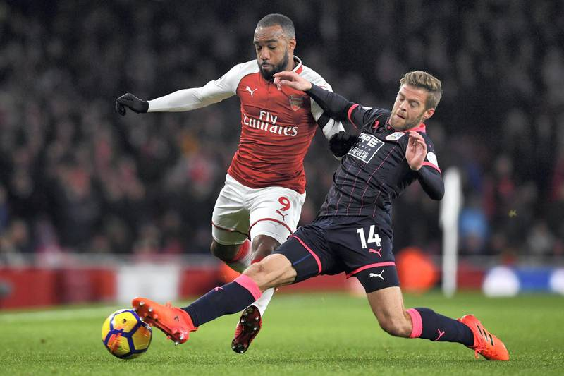 Huddersfield Town's English defender Martin Cranie (R) tackles Arsenal's French striker Alexandre Lacazette (L) during the English Premier League football match between Arsenal and Huddersfield Town at the Emirates Stadium in London on November 29, 2017.  / AFP PHOTO / Ben STANSALL / RESTRICTED TO EDITORIAL USE. No use with unauthorized audio, video, data, fixture lists, club/league logos or 'live' services. Online in-match use limited to 75 images, no video emulation. No use in betting, games or single club/league/player publications.  /