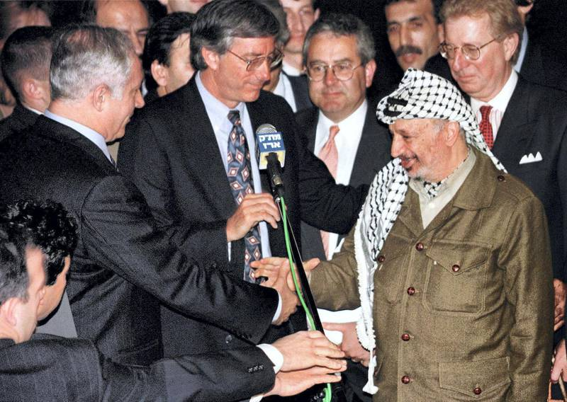 Palestinian President Yasser Arafat (R) shakes hands with Israeli Prime Minister Benjamin Netanyahu after United States' special envoy Dennis Ross (C) spoke, early January 15 after the two leaders met and agreed on the term for the long overdue Israeli troop redeployment in Hebron. The talks lasted less than two hours and concluded months of negotiations which will lead to the end of the Israeli military occupation in about 80 percent of Hebron.  MIDEAST