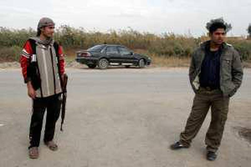In this Dec. 12, 2009, Iraqi Awakening Council members, Sunnis who turned against al-Qaida and now help Iraqi forces, provide security stand guard at a checkpoint in the Arab Jabour area south of Baghdad, Iraq. A top anti-insurgent fighter and three family members were slain overnight in their village south of Baghdad Thursday. (AP Photo/Loay Hameed)