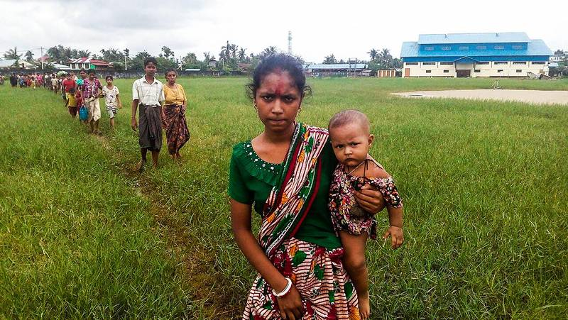 A woman holds a child in her arms as she arrives at the Yathae Taung township in Rakhine State in Myanmar after fleeing from violence in their village on August 26, 2017.  Terrified civilians tried to flee remote villages in Myanmar's northern Rakhine State for Bangladesh on August 26 afternoon, as clashes which have killed scores continued between suspected Rohingya militants and Myanmar security forces. / AFP PHOTO / Wai Moe