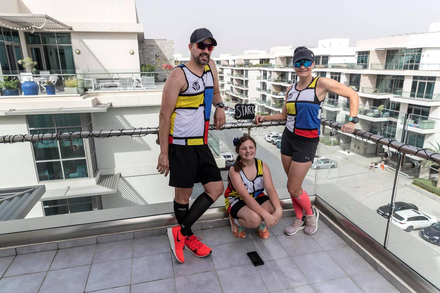 """DUBAI, UNITED ARAB EMIRATES. 28 MARCH 2020. Colin Allin and his wife Hilda along with their daughter Geena pose at their """"Start"""" section of their balcony marathon at their apartment in the Meydan Polo Residence. Colin and his wife Hilda are running a marathon on their balcony while the City of Dubai is under a Stay At Home policy to keep residence safe from the spread of Covid-19. (Photo: Antonie Robertson/The National) Journalist: Patrick Ryan. Section: Business."""