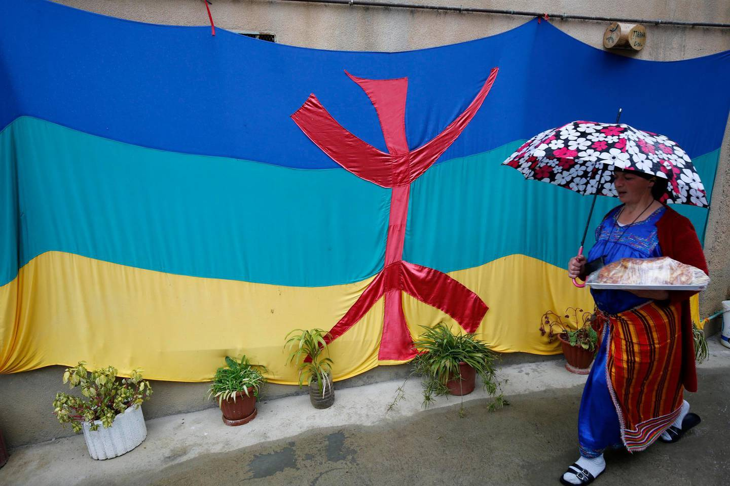 epa08122583 A woman walks next to a Berber flag as Algerian Berbers celebrate New Year 2970 in Sahel village, south of Tizi-Ouzou, east of Algiers, 12 January 2020. Berbers, an ethnic group from the pre-Arab populations of North Africa, are currently celebrating their New Year. Yennayer, the first month of the Berber Year, is marked as a national holiday in Algeria for the third time.  EPA/STRINGER
