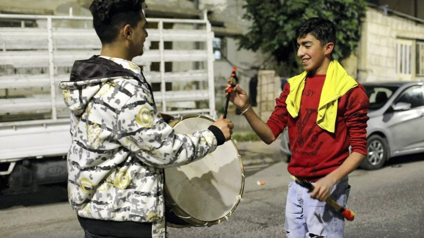 Kids take turns to pound on Musaharti Zeid Abu Mushref's drum during his nightly rounds in Amman's Nuzha district to wake people up for their pre-dawn meal during the month of Ramadan.  Courtesy of Amy McConaghy/ The National