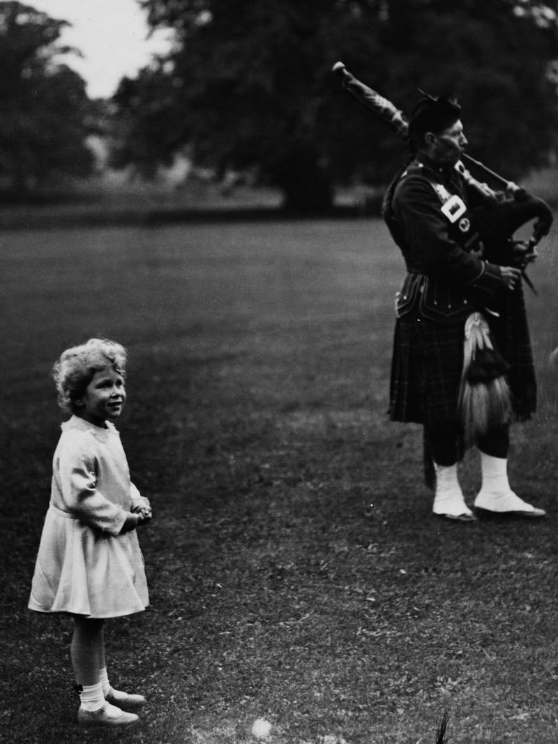 Princess Elizabeth (later Queen Elizabeth II) watches members of a pipe band play in the grounds of Glamis Castle near Forfar in Scotland in September 1929. (Photo by Topical Press Agency/Getty Images)