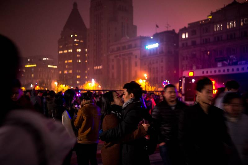 A couple kisses as people gather on the Bund along the Huangpu River during New Year celebrations in Shanghai at the start of January 1, 2018.  / AFP PHOTO / CHANDAN KHANNA
