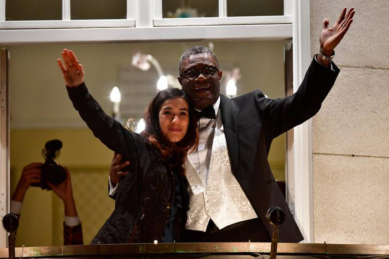 Nobel prize laureates Congolese gynecologist Denis Mukwege (R) and Iraqi Yazidi-Kurdish human rights activist Nadia Murad greet the crowd from the balcony of the Nobel suite in Oslo downtown, Norway on December 10, 2018. (Photo by Tobias SCHWARZ / AFP)