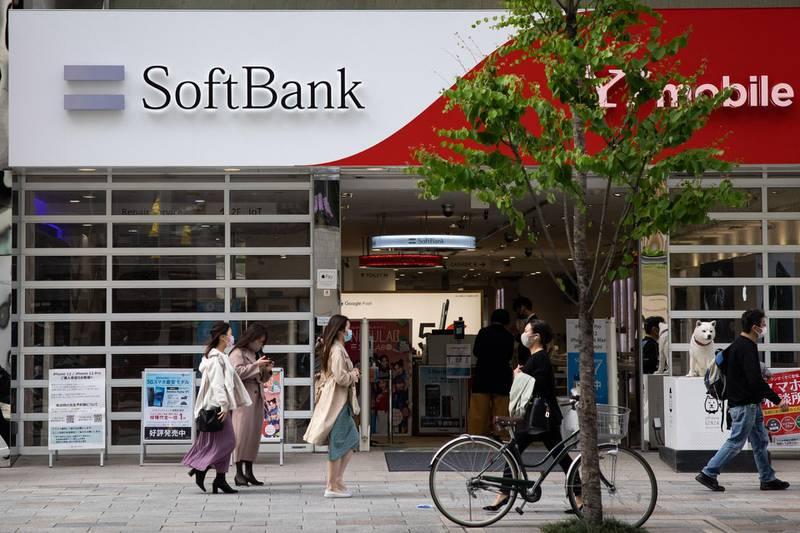 Pedestrians walk past a SoftBank mobile shop in the Ginza shopping district in Tokyo on April 6, 2021.  / AFP / Yuki IWAMURA