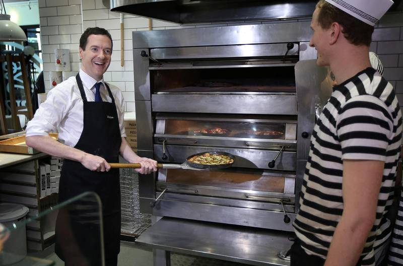 HOVE, ENGLAND - MARCH 31:  British Conservative Chancellor George Osborne (L) takes a pizza he made from the oven as staff member Will Jessell (R) looks on during a visit to a Pizza Express restaurant on March 31, 2015 in Hove, England. Campaigning, in what is predicted to Britain's closest national election, started yesterday. Polling day is on May 7, 2015.  (Photo by Peter Macdiarmid/Getty Images)